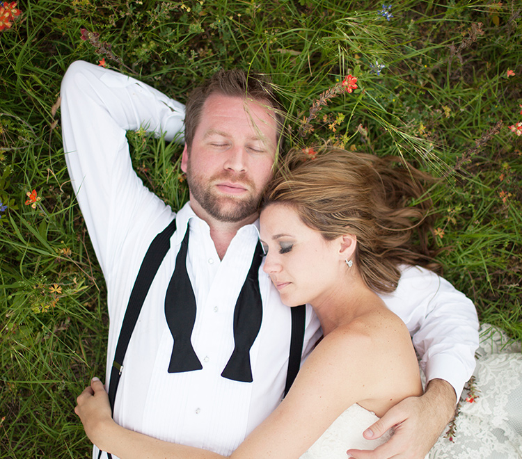 Married couple holding each other on the grass eyes closed
